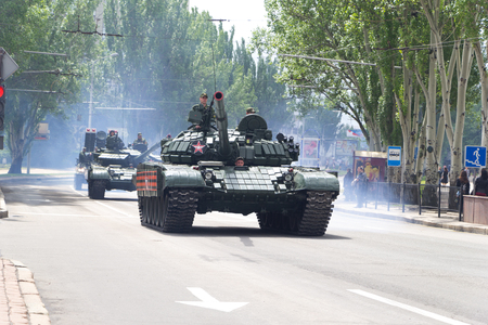 Donetsk, Donetsk People Republic, Ukraine – May 9, 2019: Armored soviet tanks T-72 driving through the main street of the Donetsk in the end of Victory Day Parade. Column of military equipment.