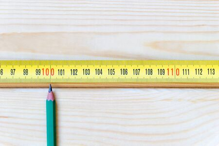 Measurement concept with copy space. A simple pencil points to the mark of one hundred centimeters on a measuring tape, lying on light wooden table. Top view. Close-up. Vertical photo with copy space. 스톡 콘텐츠
