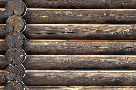 Mur de maison en bois à partir de bûches de bois. Arrière-plan avec espace de copie. Vue de face rapprochée avec intersection d'angle sur le côté gauche.