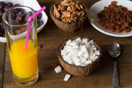 Healthy eating concept background. Top angle view of raw foods diet breakfast on wooden table. Glass of fresh orange juice, coconut meat cubes in cup from shell, kernels of walnut, raisins and dates.