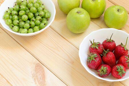 Vista dall'alto di mele verdi, fragole rosse succose e uva spina acida in ciotole bianche su un tavolo di legno luminoso. Fondo del raccolto di estate con lo spazio della copia. Cibo naturale di produzione propria. Posto per il testo personalizzato.