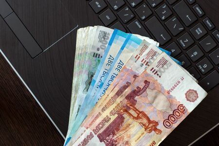 A stack of Russian rubles of different denominations lies on the laptop keyboard.