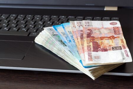 Stack of russian rubles lay on laptop keyboard