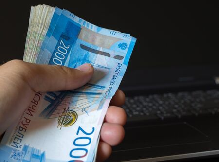 Cash in Russia. Man hand holding a bundle of Russian rubles. Banknotes 2000 rubles.