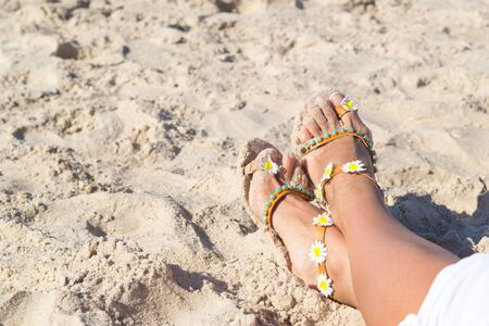 Female feet in sandals laying on golden sand on the beach. Relaxation near water concept. Summer vacation on the sea. Standard-Bild - 129137799