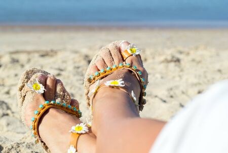 Vacation at sea. Closeup detail of female feet, golden sand on beach and blue sea water. Copy space. Beautiful woman legs, shod in white shorts and white sandals, lay on soft warm sand. Standard-Bild - 129137801