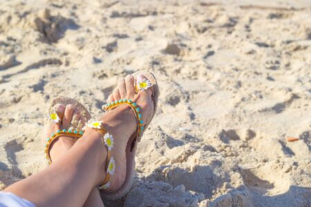 Summer relaxation on seacoast. Female feet shod in sandals lay on golden sea sand. Sandals decorated by chamomile flowers. Holidays at sea. Background with copy space. Close-up. Vacation concept. Standard-Bild - 129137796