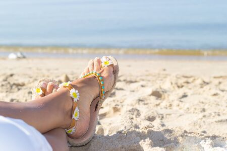 Summer vacation on the sea. Female feet in sandals laying on golden sand on the beach near seacoast.