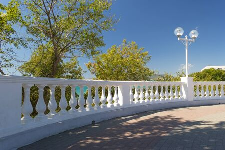 View on white stone fence with balusters from Black sea promenade on sunny early autumn day in Velvet season. Gelendzhik resort, Russia.