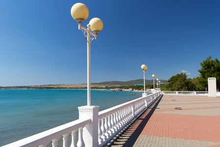 Beautiful sea promenade with white decorative fence with balusters and round lanterns in sunny autumn day. Vacation concept.