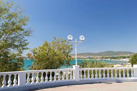 View on seascape through white stone balustrade from promenade on sunny day in Velvet season. Decorative balusters, round lanterns, green trees.