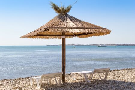 Two loungers and umbrella on a beach.