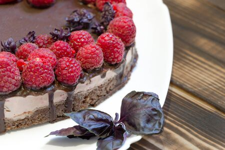 Tasty and harmless dessert background. Vegan chocolate cake with raspberries on white plate with basil leaves. Wooden table. Top angle view. 免版税图像