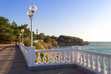 Gelendzhik embankment. Beautiful view along the fence with balustrades. Round lanterns along the promenade, green trees and the sea coast. Holidays at sea. Sunny day during vacation.