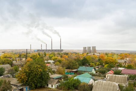 Thermal power station with residential buildings in the foreground. Smokestacks and cooling towers. Gray cloudy sky, yellowing edges of autumn trees. Air pollution concept. Environmental conservation