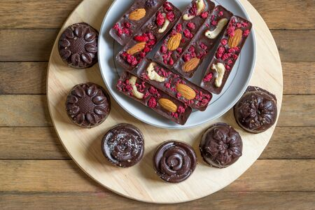 Healthy homemade recipe chocolate sticks with almonds, cashews and raspberries, and candies lie on a saucer. Round tasty sweets on a kitchen board on a wooden background. Copy space. Top view.