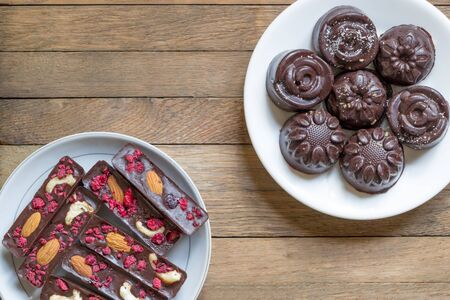 Healthy treat for tea background. Homemade vegan raw sweets on white saucers on wooden table. Sticks and candies with natural chocolate, raspberries, almond nuts and cashew. Top view. Copy space Reklamní fotografie