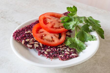 Healthy delicious raw foods snack from dried bread cracker with red tomato slice and green parsley leaves on it. Lay on white plate on kitchen table. Top angle view. Right eating concept. Vegan menu Reklamní fotografie
