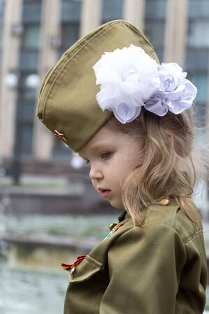 Little girl dressed in military uniform on background of fountains near the government building. White bow on her head. Children of war. Defenders of the Fatherland. Victory Day. Profile with sad look Stock Photo