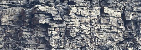 Dangerous vertical wall with protruding crumbling layered wild stone blocks. Rock cliff face background. Toned. Abstract texture for stone mining industry. Copy space for custom text Stok Fotoğraf