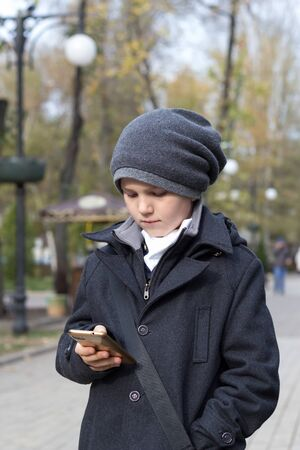 Schoolboy in hat holding smartphone in hand and dialing number on touch screen. Outdoors in park. Daytime in autumn. Child dressed in stylish business clothes. Communication by phone. Parental control