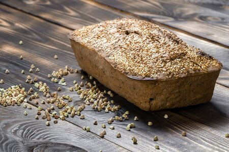 Gluten-free buckwheat bread with a golden brown crust, sprinkled with sesame seeds, lies on a wooden table. Healthy homemade recipe. Grains of green buckwheat are scattered nearby. Copy space