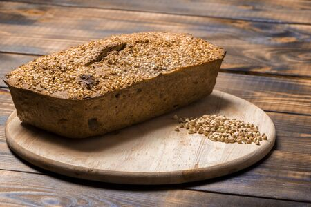 A loaf of freshly baked buckwheat bread lies on a round kitchen board on a brown wooden table. A handful of green buckwheat seeds are scattered nearby. Harmless baking for vegans and vegetarians