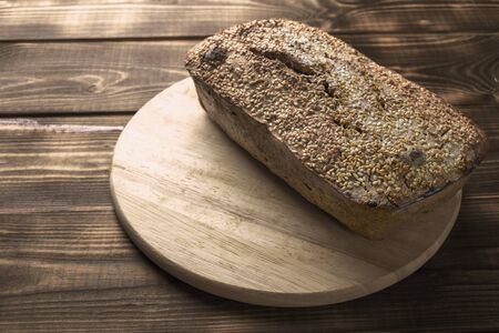 Freshly baked buckwheat bread. A loaf of bread lies on a round kitchen board on a brown wooden table. Gluten-free healthy home-made product. Natural nutrition for vegans and vegetarians. Toned 스톡 콘텐츠 - 140993374