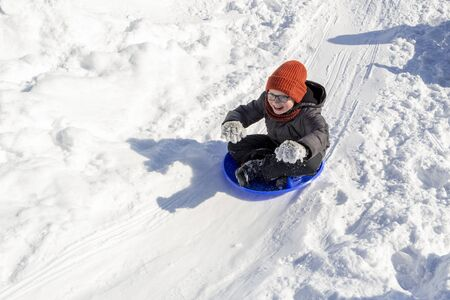 Childrens fun in the winter. Sledding from a snow slide. A smiling boy in glasses rides in a sleigh, like a rider as if he drives a horses reins. Fun in the fresh frosty air. Healthy games for kids