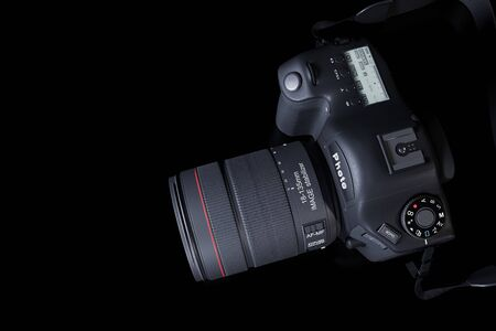 Top view professional digital camera with a zoom lens and a leather strap on a black background with copy space. View from above. Realistic 3d render. Place for advertising text. Reflection at bottom. 免版税图像