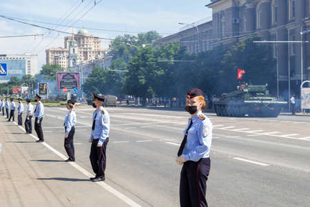 Donetsk, Donetsk People Republic, Ukraine, June 24, 2020: A column of heavy military equipment move along the main street of the city during the Victory Parade. Policemans in foreground. 新聞圖片