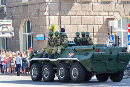 Donetsk, Donetsk People Republic, Ukraine - June 24, 2020: A column of armored personnel carriers with armed soldiers in full outfit on armor move along the city center during the Victory Parade.