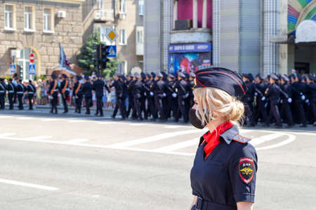 Donetsk, Donetsk People Republic - June 24, 2020: Lovely policewoman in foreground in mask from coronavirus. Police march along the main street of the city in the background during the Victory Parade.