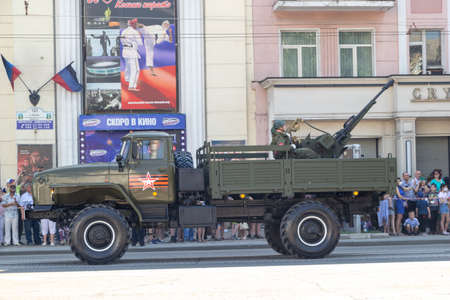 Donetsk, Donetsk People Republic, Ukraine, June 24, 2020: Soviet military trucks with anti-aircraft machine guns on board ride in the city center during the Victory Day parade.