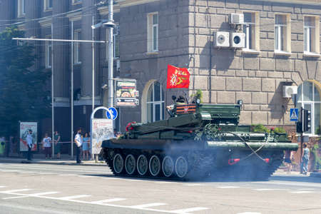 Donetsk, Donetsk People Republic, Ukraine, June 24, 2020: A column of Soviet military equipment with soldiers on it move along the main street of the city during the Victory Parade.
