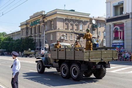 Donetsk, Donetsk People Republic - June 24, 2020: Soviet military trucks with heavy machine-guns and soldiers in oldstyle uniform on it moving on Artema streen during a Victory Parade.