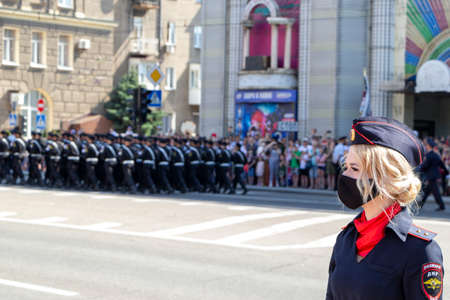Donetsk, Donetsk People Republic - June 24, 2020: Policewoman in foreground in mask from coronavirus. Troops march along the main street of the city in the background during the Victory Parade.
