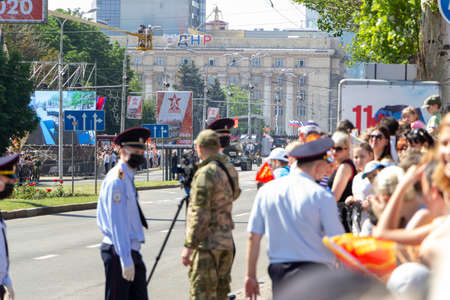 Donetsk, Donetsk People Republic, June 24, 2020: A crowd of people on the main street of the city during the Victory Parade. The police are holding back the movement. Military equipment moving.