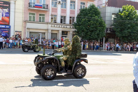 Donetsk, Donetsk People Republic, Ukraine - June 24, 2020: A military ATV with a pilot and a sniper in full gear on board moves along the main street of the city during the Victory Parade.