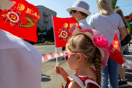 Donetsk, Donetsk People Republic, Ukraine - June 24, 2020: Young children stand with flags and await the display of armored vehicles during the Victory Parade on the main street of the city.