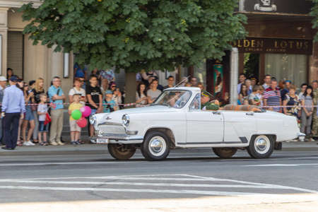 Donetsk, Donetsk People Republic, Ukraine - June 24, 2020: White Volga cabriolet with a serviceman at the wheel leads the Victory Parade. Artema street.