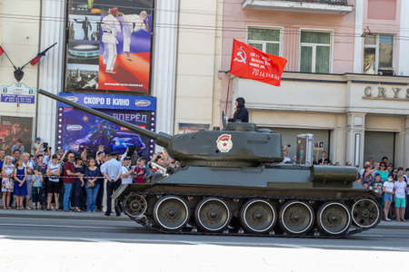 Donetsk, Donetsk People Republic, Ukraine - June 24, 2020: Soviet tank T-34 rides along the Artema street during the Victory Parade with the flag of the Red Army USSR. A crowd takes a pictures.