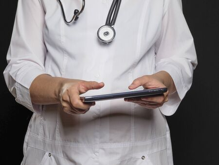 A female doctor in a white coat holds a tablet in her hands posing on a black background. Doctor template.
