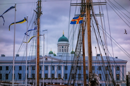 engel:  Masts of the sailing ships in front of the Helsinki City Hall with Helsinki Cathedral on the background during an annual Baltic herring fair at market square.