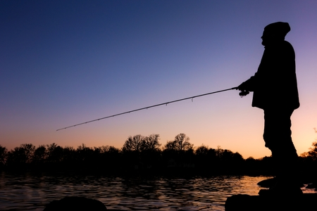 Silhoutte of a sportsfisheman standing on a rock and fishing on a bay in Blekinge Sweden at sunset time photo