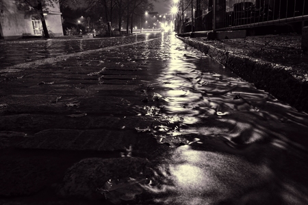 Rain water flowing down a street in down town Helsinki during a nightly autumn storm and creating miniature surge on a cobble street at Unioninkatu in Kaisaniemi district.