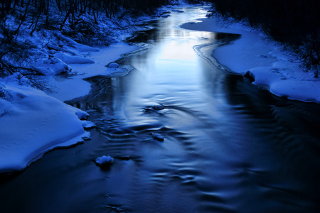 bourn: Icy water flowing slowly in an almost completely frozen river after sunset in an evening dusk in Helsinki Finland.