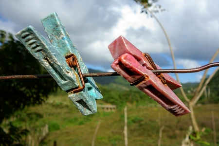 outworn: Two old and weary clothespin as friends on an outdoors clothes line in a tropical setting in Manicaragua Cuba on Christmas eve 2013. Stock Photo