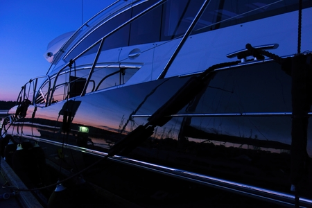 Yacht at the marina captured during a blue hour with setting sun coloring the horizon and reflection of a boat and marina visible from the yacht side.