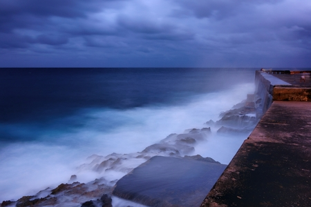 bounding: Evening by the walls of the Malecn esplanade in Havana Cuba and dramatic sea bounding water on the rocks.